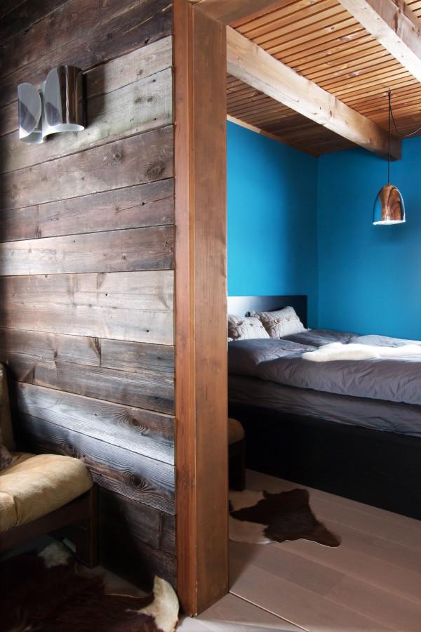 Wand mit Altholz mit Blick in ein Schlafzimmer der Almhütte